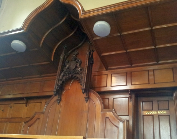 The royal coat of arms above the judge's chair