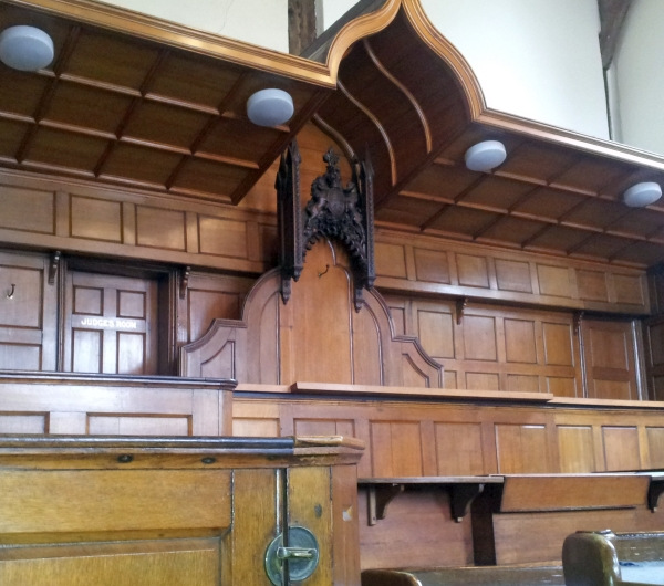 Judge's chair with coat of arms above it